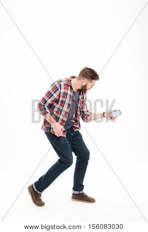 Full length portrait of a casual bearded man listening music and playing invisible guitar over white background