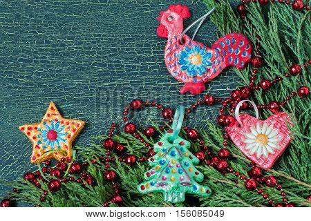 Making homemade toy for the Christmas decorations from salt dough with your hands. Children's art project. DIY concept. Festive background with fir branches and homemade toys. Space for text