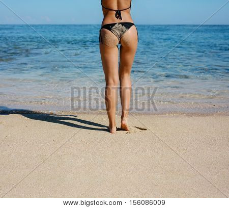 Rear view of young woman in bikini covered with sand standing on the beach. Low section shot of female standing on the sea shore.