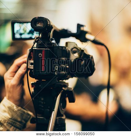 Television camera at press conference, toned image