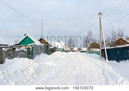 snowy winter road runs through the village with build