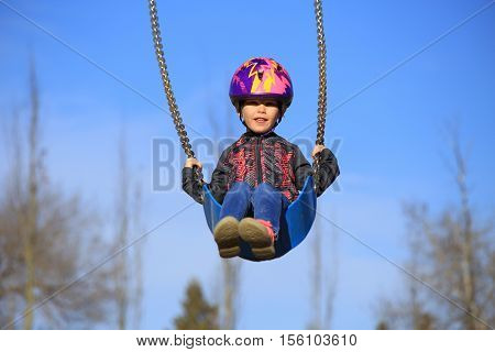 A four year old girl wearing a bicycle helmet swinging on a swing