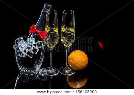 Bottle of champagne in an ice bucket with two wineglasses and orange