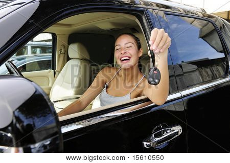happy woman showing keys of her new expensive status car