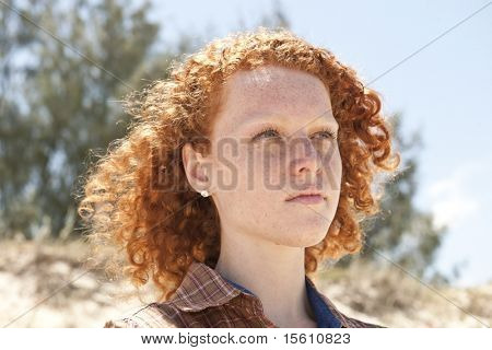 Portrait of a young woman with red hair at the beach