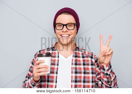 Happy Man In Hat And Glasses Holding Cup Of Tea And Showing V-sign