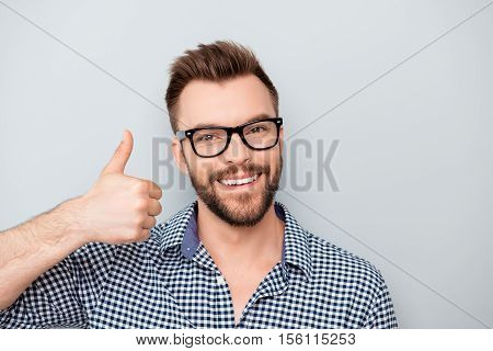 Happy Young Smiling Man In Glasses Showing Thumb Up