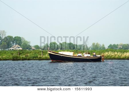 a sloop with passengers on the river