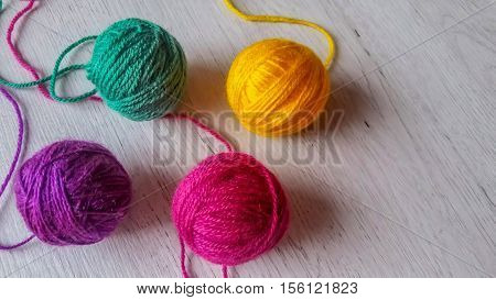 Wool yarn in rainbow colors on a dark wooden background