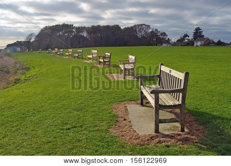 A Line of park benches Suffolk England.