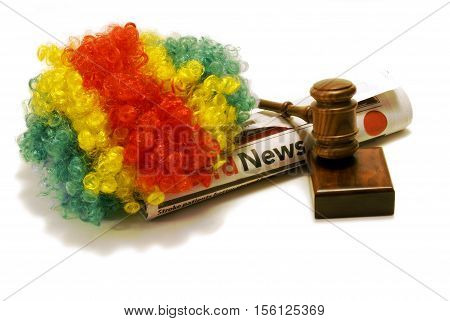 An isolated clowns wig newspaper and gavel to illustrate how clowns have been an issue across the nation this year.