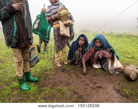 SEMIEN MOUNTAINS ETHIOPIA - JULY 01 2016: Children in Semien Mountains Ethiopia playing mancala game on a foggy day.