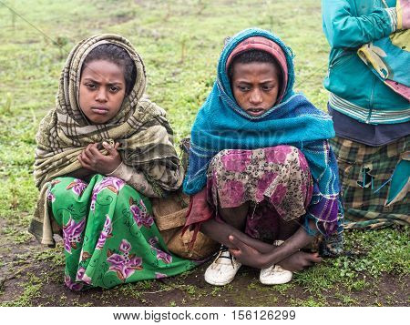 SEMIEN MOUNTAINS ETHIOPIA - JULY 01 2016: Girls selling souvenirs in Semien Mountains Ethiopia on a foggy day.