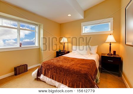 Bedroom With Yellow Mustard Paint And Brown Bedding