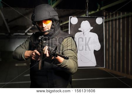 A man in a vest shot at the shooting range with a rifle