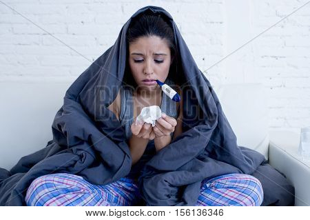 young attractive hispanic woman lying sick at home couch in cold flu sneezing nose with tissue using thermometer covered with blanket in gripe disease symptom and health care concept