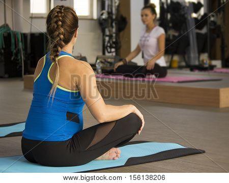 Women sitting cross legged in yoga class at the ym.