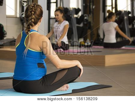 Pregnant women in maternity yoga at the gym.