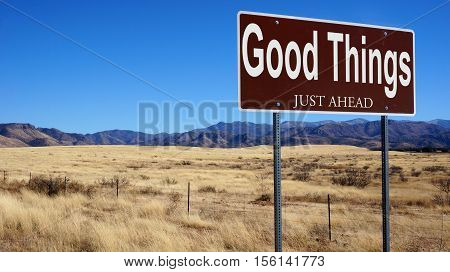 Good Things Just Ahead brown road sign with blue sky and wilderness