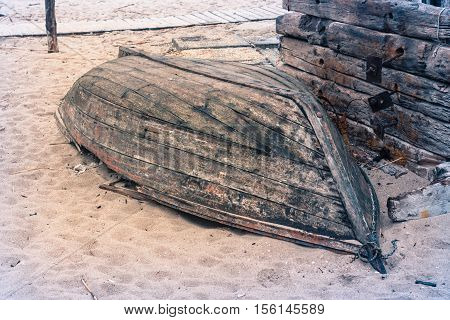 Old fishing boat broken after storm. it is lying upside down on the sand