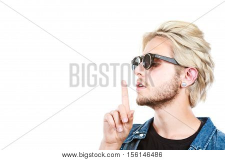 Men fashion accessories hairstyle modeling concept. Artistic hipster blonde man wearing sunglasses showing silence gesture finger on lips profile portrait studio shot isolated