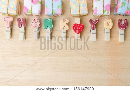 Thank you word of clothesline with gift boxes on wooden background