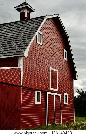 A partial image of a large red barn against a cloudy sky.