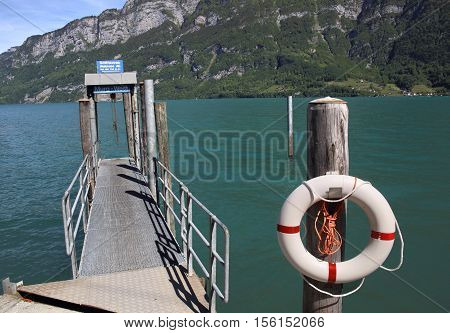 MURG, SWITZERLAND - NOV 10, 2015: Pier at Murg facing Lake Walen on Nov 10, 2015 in Murg, Switzerland. Lake Walen is a beautiful lake near Zurich.