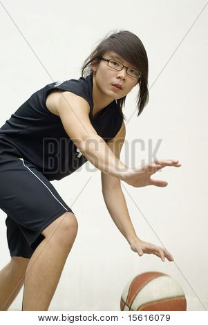 Asian basketball player defending ball