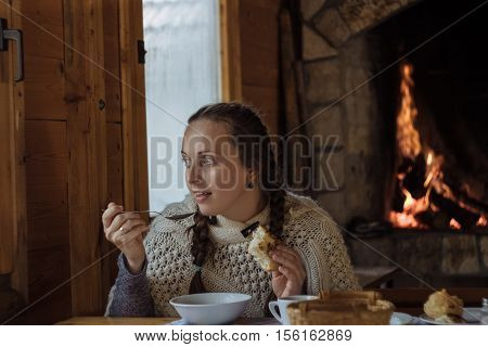 Young Woman Eating Soup In A Wooden Cafe On The Background Of The Furnace