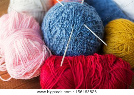 handicraft and needlework concept - knitting needles and balls of yarn on wood