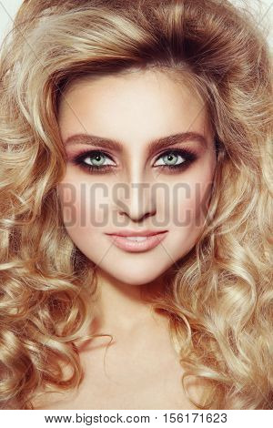 Vintage style portrait of young beautiful girl with long curly hair and stylish make-up