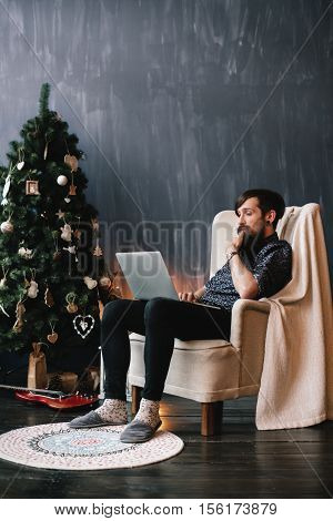 View of stylish brunet hipster sitting on armchair, using laptop and fingering his beard. Copyspace