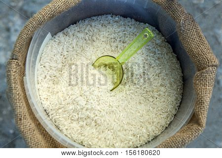 White long rice in a sack and plastic scoop
