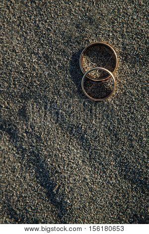 Wedding rings on the beach. Closeup view.