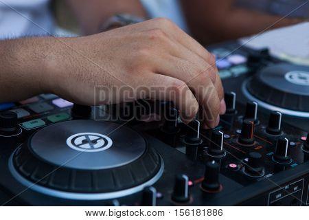 Operators hand a on dj mixer controller.