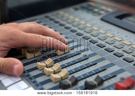 Operators hand on a sound mixer controller.