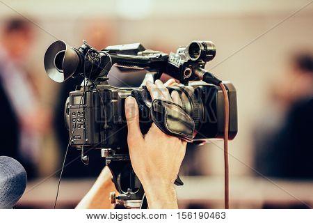 TV camera recording press conference, toned image, horizontal