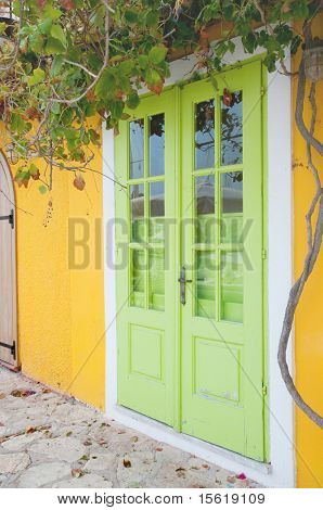 Green Greek double door in yellow house