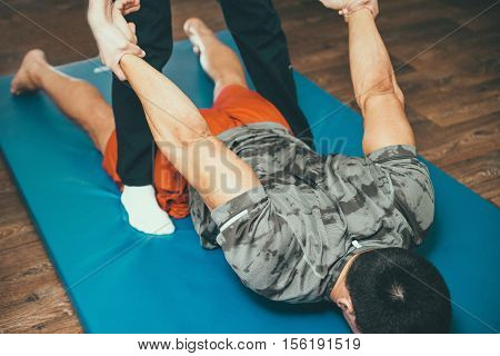 Physical therapist working with male patient. Streching patient's back