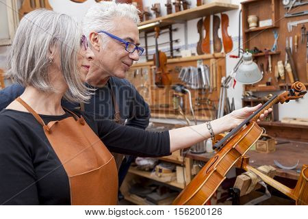 Group Of Mature Violin Maker In Pose While Testing The Violins In His Laboratory
