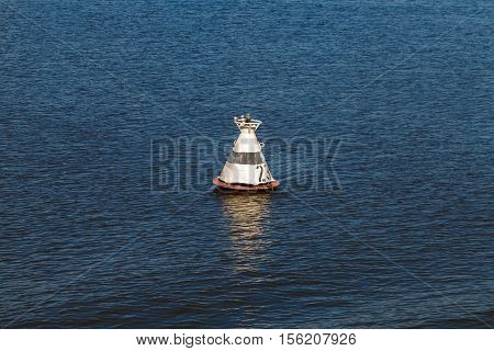 White buoy on the blue water surface of the river