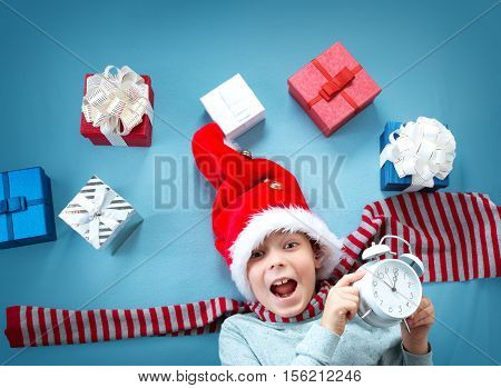 Happy child on blue blanket in red hat with alarm clock. Cute boy in christmas cap with many presents