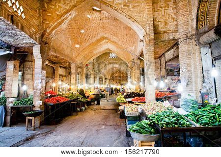ZANJAN, IRAN - OCT 7, 2014: Buyers select fresh fruits and vegetables under the ancient vaults of Eastern Bazaar on October 7, 2014. With a population of 400.000 Zanjan is the 20th largest city in Iran