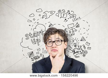Bespectacled businessman is standing near a concrete wall with startup sketch on it