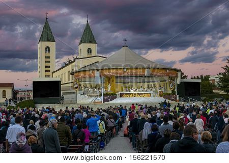 MEDJUGORJE BOSNIA AND HERZEGOVINA October 04 2016. Thousands of pilgrims attending a holy mass/service in the evening. Dramatic blue and purple clouds and sky behind the Saint James church.