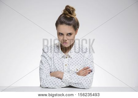 Cross girl in polka shirt is sitting with her hands crossed. Concept of being offended. Mock up