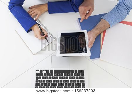 Top view of woman's hands in blue blazer and man's hands in a shirt. She is taking notes. He is holding a tablet and pointing at the screen. Mock up