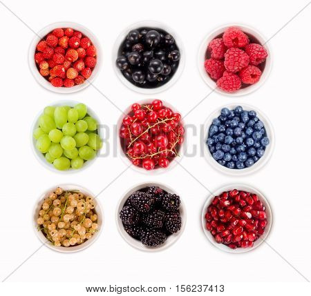 Set various berries. Strawberries, currants, raspberries, grapes, pomegranates, blueberries and blackberries. Collage of different fruits and berries isolated on white. Ripe and tasty berry.