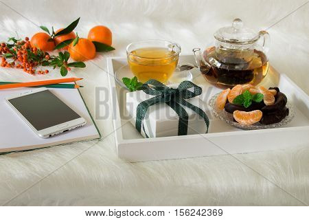 Green mint tea mandarin slices chocolate and gift box on tray near notebook pens mobile mandarins mountain ash sprig on white artificial fur background. Happy time break and gift.